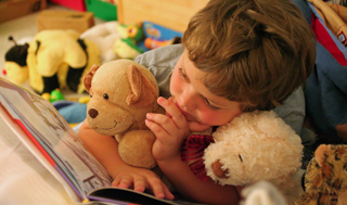 boy with stuffed toys reading