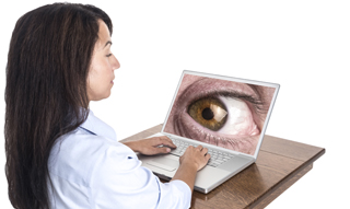 A young mixed race woman types on her laptop computer while she is being watched by a giant eye on the laptop screen.
